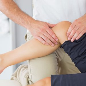 A massage therapist giving a massage to sportsman's knee during a physio session.