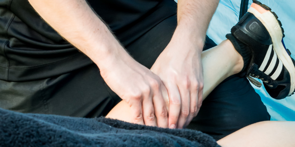 A trained professional giving a massage to an athelete's calf muscle during massage therapy.